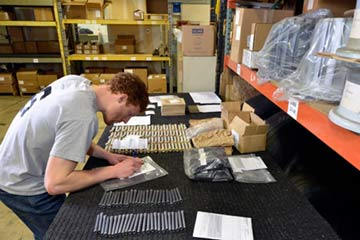 An employee diligently packs small aircraft parts into boxes